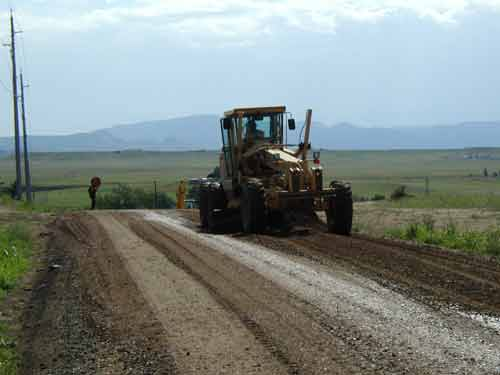 A tractor pushes dirt to level out a country road